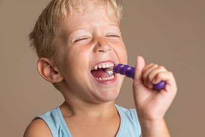 A blonde boy smiles and brushes his teeth with a purple children's toothbrush